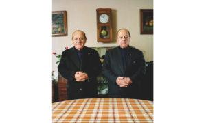 abbés jumeaux en col romain dans leur salle de séjour