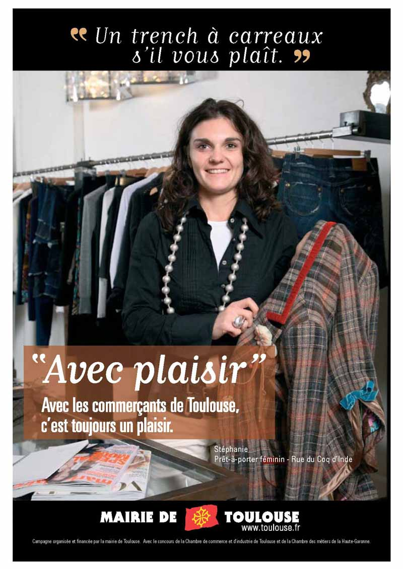 La vendeuse pose dans son magasin de prêt à porter une veste à la main