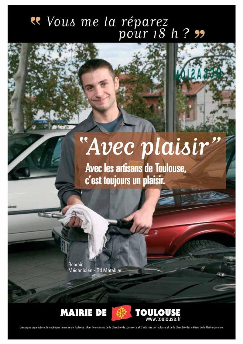 Un jeune mécanicien pose dans son garage, une clef à la main