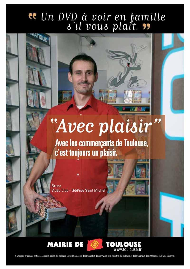 Un loueur de DVD pose dans sa boutique des dvd à la main Avec plaisir, campagne de communication de la ville de Toulouse et de la chambre de Commerce et d'Industrie de Haute-Garonne