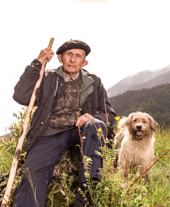 Un vieux berger, est assis sur un rocher son chien labry prés de lui. Il a un béret sur la tête