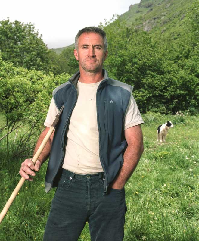 Un berger en estive a sa canne de berger à la main, son chien surveille le troupeau derrière lui