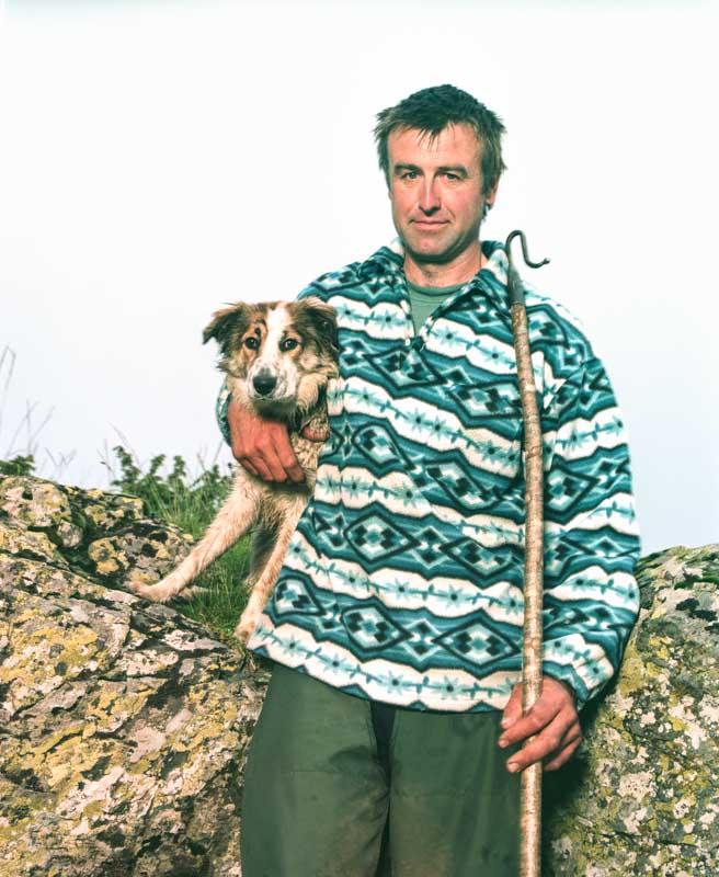 Un berger, appuyé contre un rocher tient son chien d'une main et sa canne de berger de l'autre