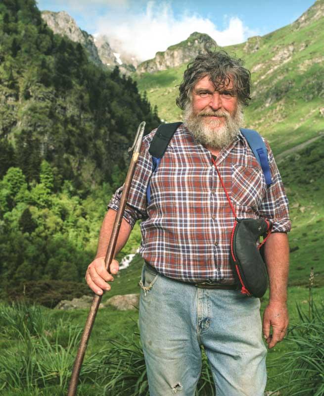 Un berger à la généreuse barbe et cheveux au vent, sa canne de berger à la main sur les cimes des Pyrénées