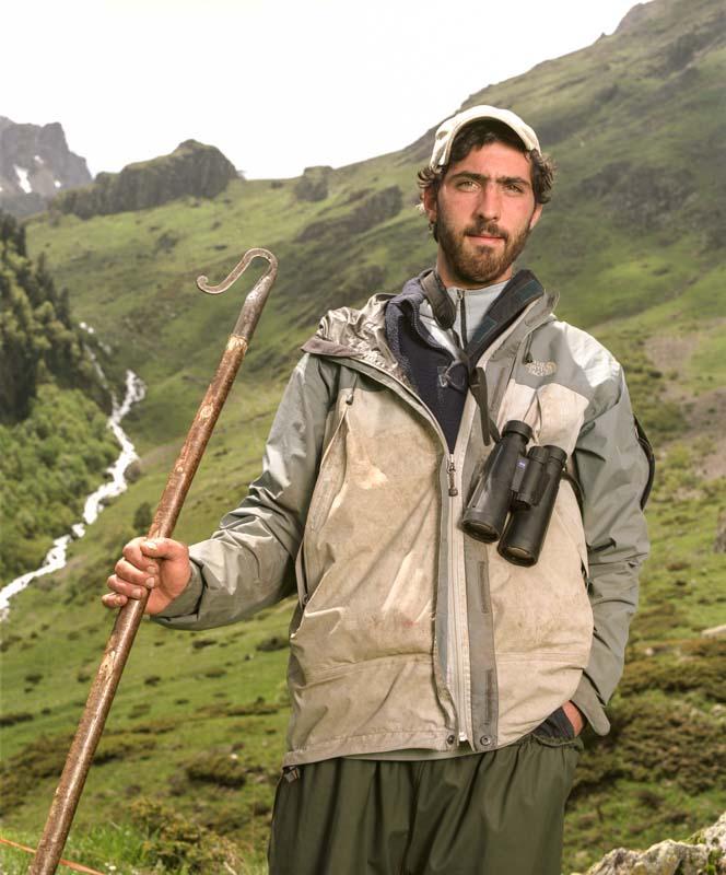 Un jeune berger à la barbe brune tien sa canne de berger au bord d'un torrent sur les hauteurs des Pyrénées