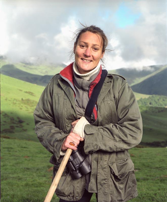Une vachère son baton à la main et jumelles au cou surveille de loin les déplacements de son troupeau dans les estives des Pyrénées