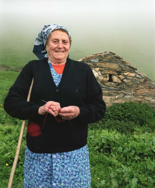 Une bergère dans les Pyrénées tricote prés de sa cabane en surveillant ses brebies
