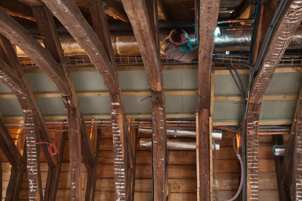 Chantier de rénovation Musée Toulouse-Lautrec d'AlbiUn plombier soude des tuyaux sous une magnifique charpente